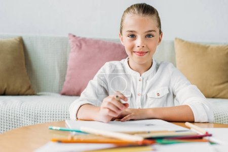 adorable little child drawing with color pencils and looking at camera
