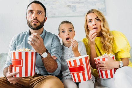 shocked young family watching movie at home with buckets of popcorn