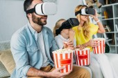 excited young family in virtual reality headsets watching movie with buckets of popcorn