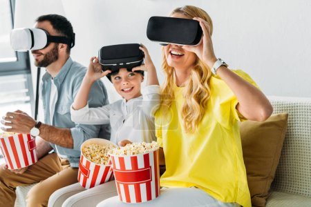 happy young family in virtual reality headsets with buckets of popcorn