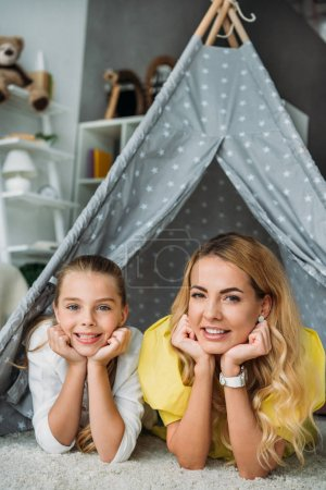 mother and daughter lying in teepee and looking at camera at home