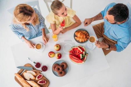 Photo pour Vue de dessus de belle jeune famille prenant le petit déjeuner ensemble - image libre de droit