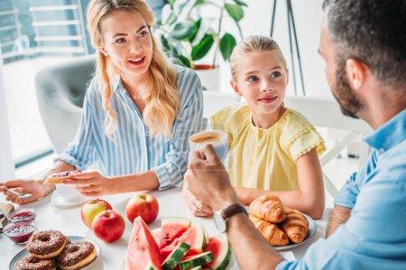 Photo pour Sourire jeune famille prendre le petit déjeuner ensemble à la maison - image libre de droit