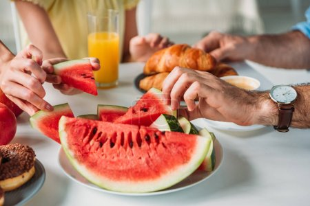 cropped shot of family taking watermelon slices from plate