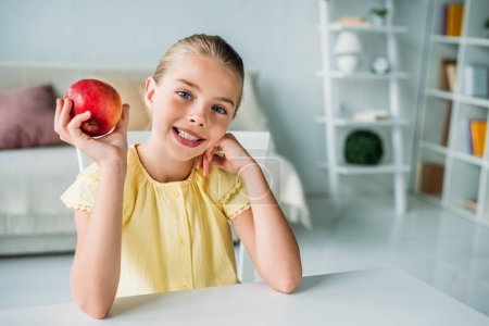 Photo for Adorable little child with red apple sitting at home - Royalty Free Image