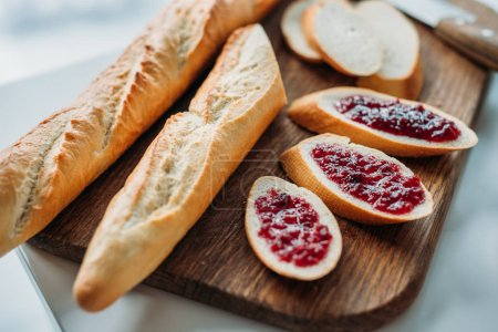 close-up shot of sliced baguette with jam on wooden cutting board