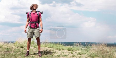 Photo for Handsome traveler with backpack standing at summer meadow - Royalty Free Image