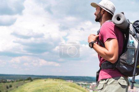 Photo pour Touriste masculin en chapeau avec sac à dos regardant prairie d'été - image libre de droit