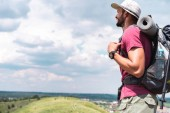 male tourist in hat with backpack looking at summer meadow