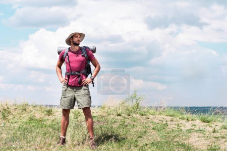 traveler with backpack and tourist mat standing at summer meadow