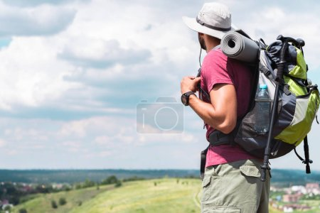 male traveler in hat with backpack and tourist mat looking at summer meadow
