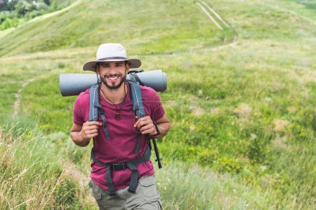 happy traveler in hat with backpack and tourist mat