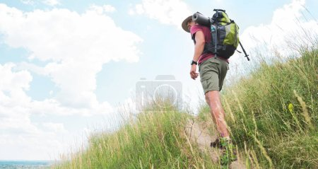 male hiker in hat with backpack and tourist mat walking on path