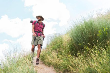 hiker in hat with backpack and tourist mat walking on path