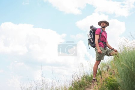 male hiker in hat with backpack and tourist mat