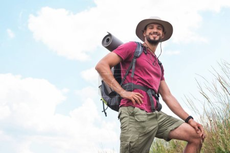 Photo for Smiling hiker in hat with backpack and tourist mat - Royalty Free Image