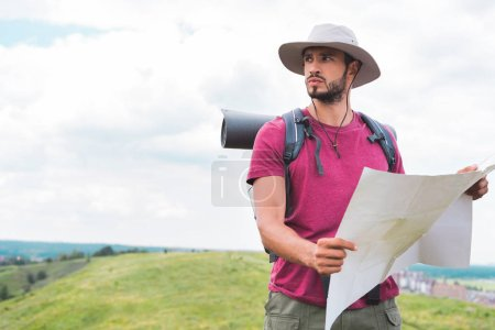 Photo for Young traveler in hat with backpack holding map on summer meadow - Royalty Free Image