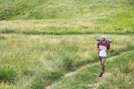 traveler with backpack holding map and walking on path on summer meadow