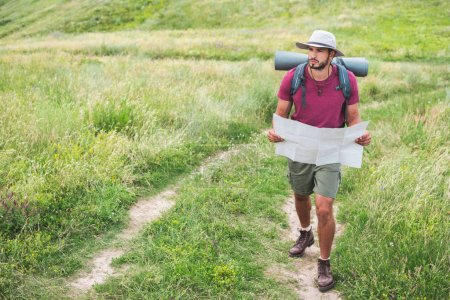 hiker in hat with backpack holding map and walking on path