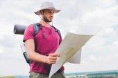 handsome hiker in hat with backpack looking at map