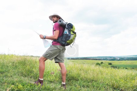 hiker with backpack holding map and standing on green field