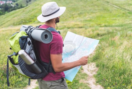 male hiker in hat with backpack, thermos, tourist mat and map