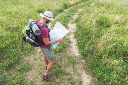 male traveler in hat with backpack, thermos, tourist mat looking at map