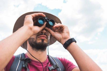 handsome male tourist in hat looking in binoculars