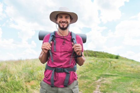 smiling hiker in hat with backpack walking on green field