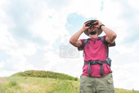male traveler in hat with backpack looking in binoculars