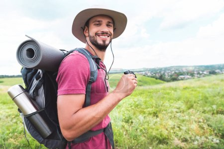 smiling traveler in hat with backpack holding binoculars on meadow