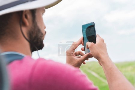Photo for Male tourist with backpack taking photo on smartphone on meadow - Royalty Free Image