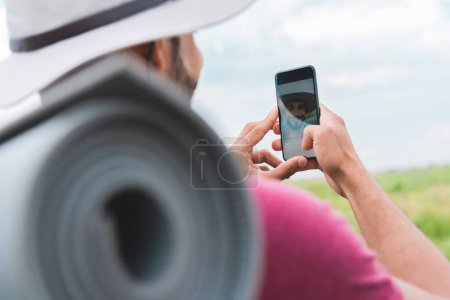 Photo for Hiker with backpack and tourist mat taking selfie on smartphone - Royalty Free Image