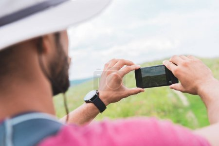 Photo for Tourist with backpack taking photo on smartphone on green meadow - Royalty Free Image