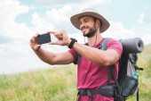 traveler with backpack taking photo on smartphone on summer meadow