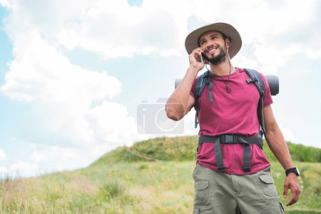 traveler with backpack talking on smartphone on summer meadow