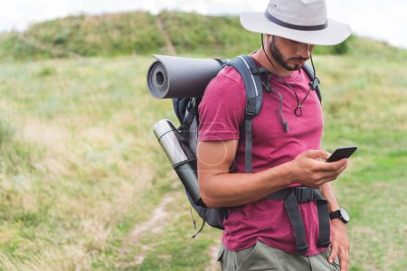 tourist in hat with backpack using smartphone on summer meadow