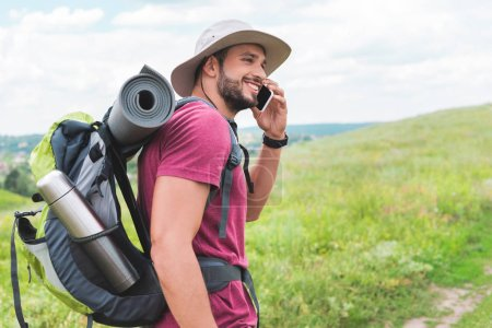 traveler with backpack talking on smartphone on green meadow