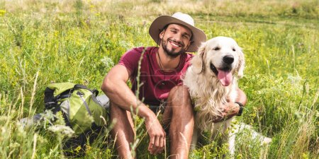 traveler sitting with golden retriever dog on green meadow