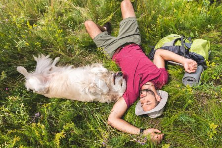 top view of traveler and golden retriever dog lying on green grass with backpack