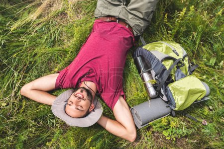 top view of young tourist with relaxing on grass with backpack, tourist mat and thermos