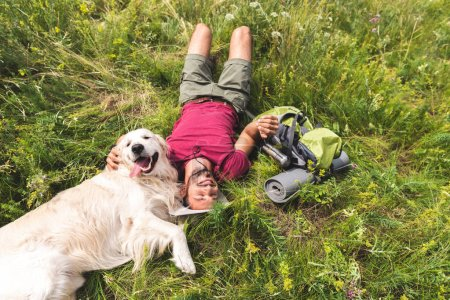 top view of happy tourist and golden retriever dog lying on green grass