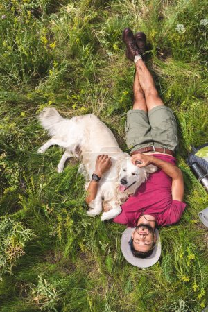 top view of tourist and golden retriever dog lying on green grass