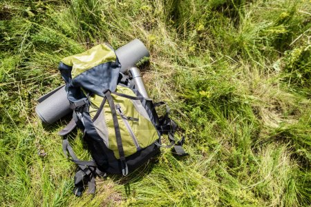 high angle view of backpack with tourist mat and thermos on green grass outdoors