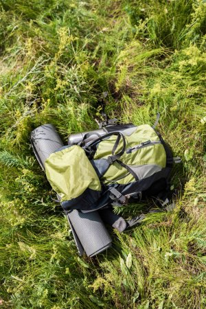 top view of backpack with tourist mat and thermos on green grass