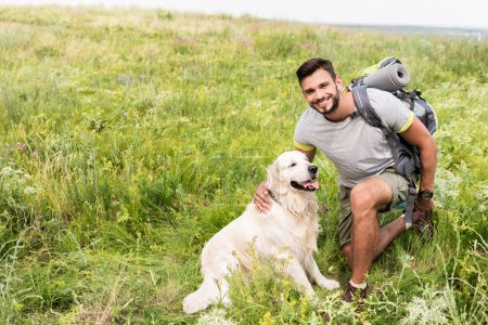 smiling traveler with backpack and cute dog sitting on green meadow