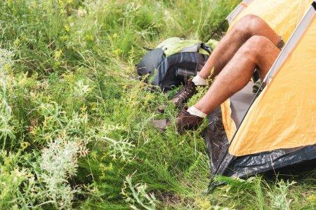 Photo pour Recadrée vue de touriste assis sous une tente jaune avec sac à dos sur l'herbe - image libre de droit
