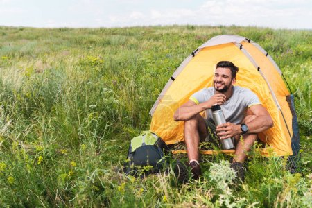 tourist with backpack and thermos sitting in yellow tent on summer meadow