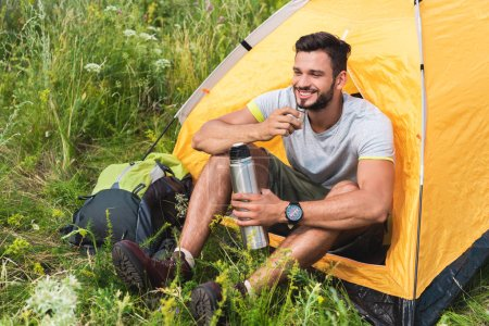 smiling traveler sitting in yellow tent with backpack and drinking coffee from thermos