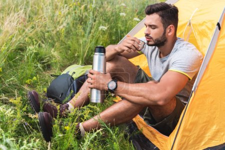 tourist sitting in yellow tent and drinking coffee from thermos
